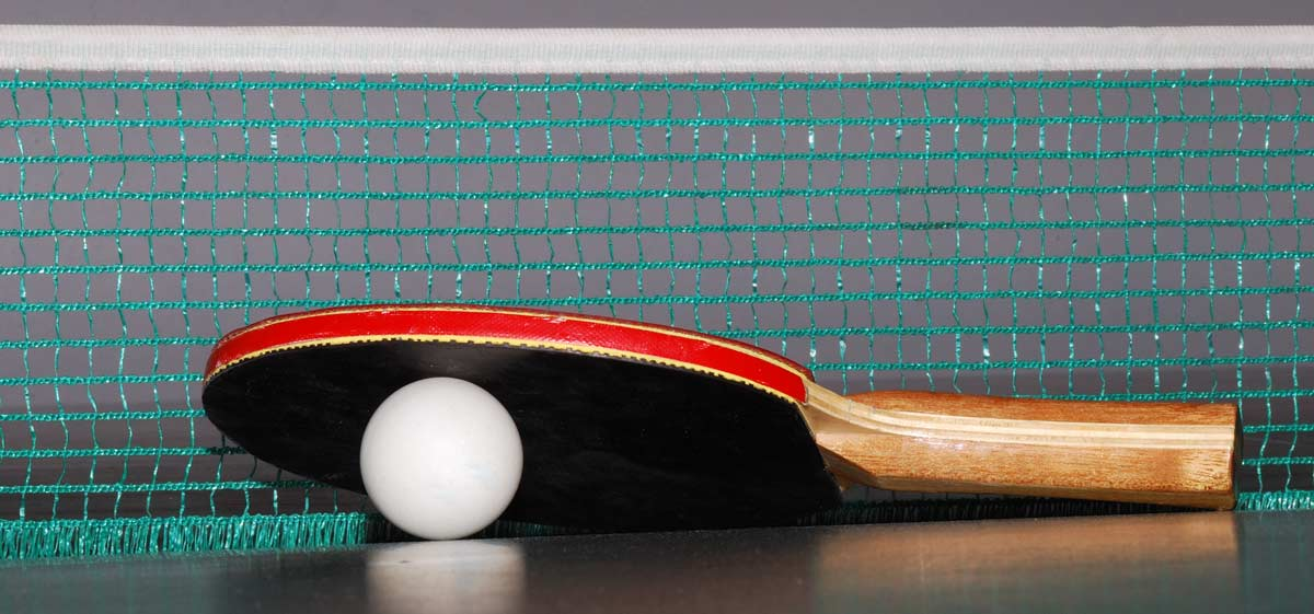 A bat and ball next to a ping pong net